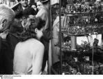 Passanten betrachten deutsches Kriegsspielzeug in einer Schaufenstervitrine