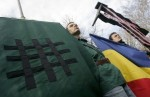 Romanians carry Romanian flag and the Iron Guard sign during a commemoration of Zelea Codreanu's death near Bucharest